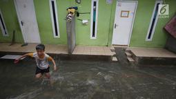 Seorang anak bermain air banjir di kawasan Jatipadang, Jakarta, Rabu (22/11). Jebolnya tanggul Kali Pulo di kawasan tersebut menyebabkan puluhan rumah terendam banjir. (Liputan6.com/Immanuel Antonius)