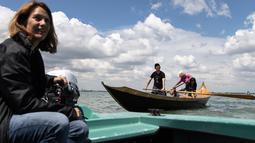 Jane Caporal, anggota Row Venice, mengajarkan mendayung gondola bagi wisatawan di sebuah kanal di Venesia, Italia pada 16 Mei 2019. Pengalaman ini bisa dimiliki dengan €85 atau sekitar Rp 1,37 juta per gondola selama 90 menit untuk empat orang yang dimulai pukul 10.00 pagi. (MARCO BERTORELLO/AFP)