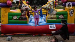 Seorang ibu menemani anaknya bermain di ruang kota Jalan Inpeksi Tanah Kusir, Jakarta, Senin (19/4/2021). Jalan Inpeksi Tanah Kusir ini menjadi salah satu tempat pilihan warga untuk menghabiskan waktu sembari menunggu berbuka puasa atau ngabuburit. (Liputan6.com/Johan Tallo)