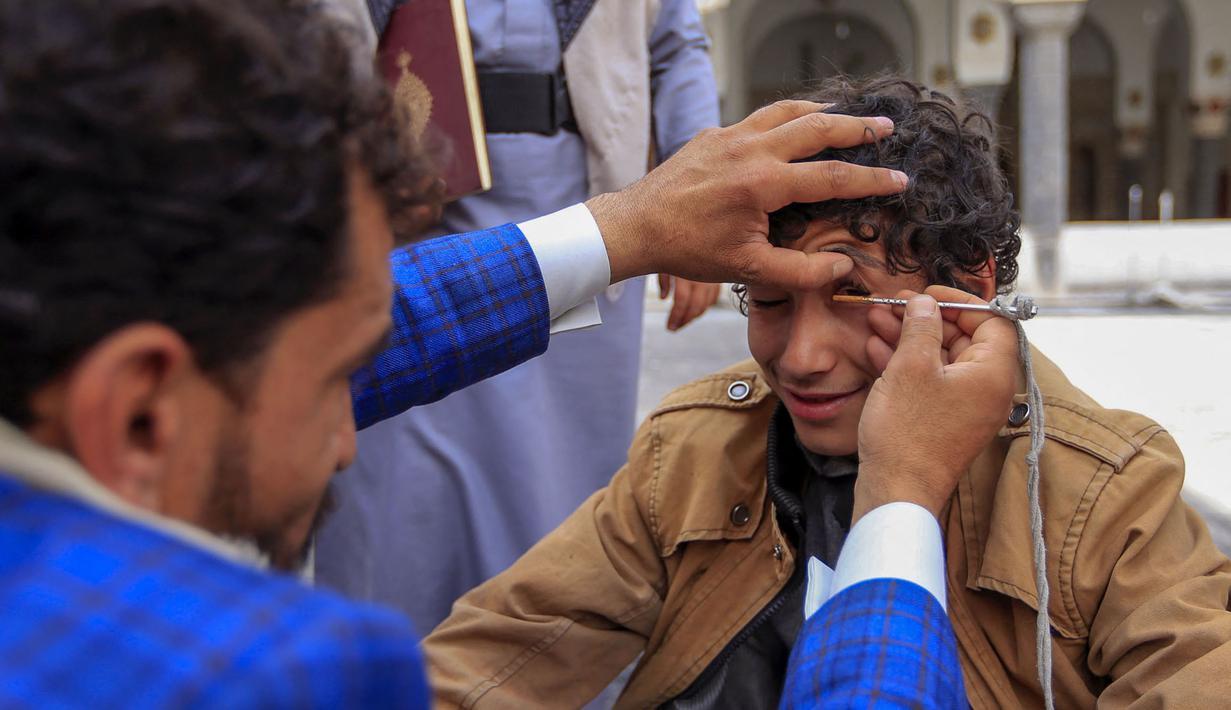 Seorang pria Yaman mengoleskan kosmetik tradisional Kohl ke kelopak mata remaja selama bulan puasa Ramadhan di Masjid Sanaa (16/4/2021).  Di Yaman, salah satu tradisi khas menandai Ramadhan yang masih lestari adalah aksi para pemuda yang merias mata dengan kohl. (AFP/ Mohammed Huwais)