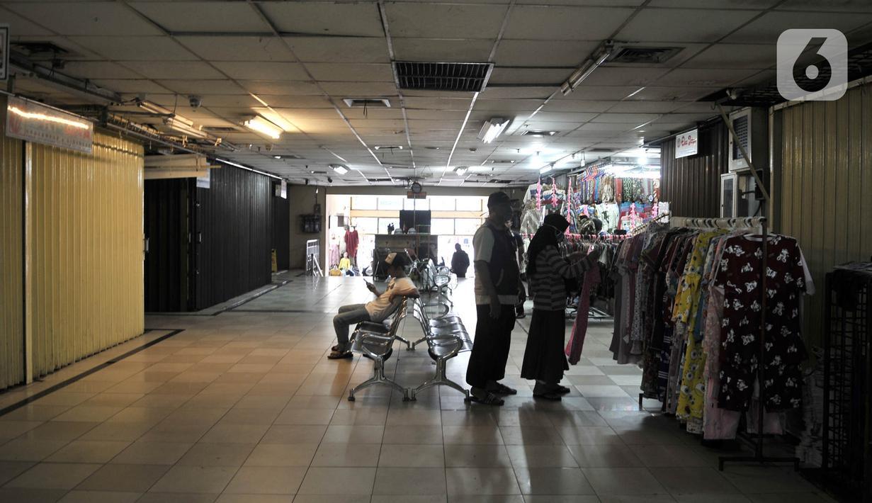 Aktivitas pedagang di dekat pertokoan yang tutup di Pasar Jatinegara, Jakarta, Kamis (26/3/2020). Sepinya pengunjung akibat larangan keluar rumah semenjak merebaknya pandemi Covid-19 menyebabkan sekitar 50 persen pedagang di Pasar Jatinegara tutup sementara. (merdeka.com/Iqbal S. Nugroho)