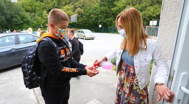 Seorang guru mendisinfeksi tangan siswa pada hari pertama tahun ajaran baru di Ozalj, Kroasia, 7 September 2020. Pembelajaran sekolah di Kroasia ditangguhkan sejak pertengahan Maret akibat wabah COVID-19. (Xinhua/Pixsell/Kristina Stedul Fabac)