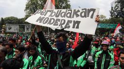 Pengemudi ojek online membentangkan poster saat menggelar aksi di seberang Istana Merdeka, Jakarta, Selasa (27/3). Mereka juga meminta legalitas angkutan ojek online. (Liputan6.com/Arya Manggala)