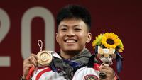Lifter Indonesia Rahmat Erwin Abdullah merayakan di podium setelah memenangkan medali perunggu cabang angkat besi 73 kg putra Olimpiade Tokyo 2020 di Tokyo, Jepang, Rabu (28/7/2021). Rahmat Erwin Abdullah berhasil menyumbang medali perunggu untuk Indonesia. (AP Photo/Luca Bruno)