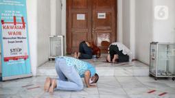 Sejumlah warga melaksanakan salat zuhur di halaman depan Masjid Cut Meutia, Jakarta, Jumat (18/9/2020). Pemprov DKI Jakarta kembali meniadakan kegiatan ibadah salat Jumat dan salat lima waktu berjemaah di semua Masjid Raya selama PSBB. (Liputan6.com/Faizal Fanani)
