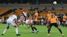 Striker Olympiacos, Ahmed Hassan, melepaskan tendangan saat menghadapi Wolverhampton Wanderers pada laga leg kedua babak 16 besar Liga Europa 2019/2020 di Molineux Stadium, Jumat (7/8/2020) dini hari WIB. Wolverhampton menang 1-0 atas Olympiacos. (AFP/Lindsey Parnaby)