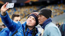 Seorang penggemar berselfie dengan penyerang Chelsea, Callum Hudson-Odoi selama sesi pelatihan di NSC Olympiyskiy, Kiev, Ukraina (13/3). Chelsea akan bertanding melawan Dynamo Kiev pada leg kedua babak 16 besar Liga Europa. (Reuters/Valentyn Ogirenko)