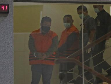 Dua tersangka kasus korupsi bansos Covid-19 digiring petugas di Gedung KPK, Jakarta, Minggu (6/12/2020) dini hari. KPK menahan tiga orang tersangka korupsi bansos di Kemensos, yaitu Matheus Joko Santoso, Ardian IM dan Harry Sidabuke. (Liputan6.com/Herman Zakharia)