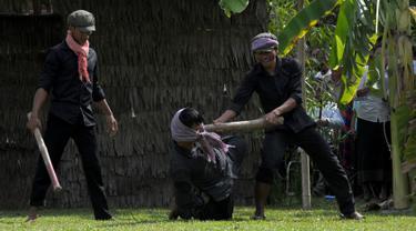 Sejumlah aktor memperagakan pembunuhan massal yang dilakukan prajurit Khmer Merah saat berkuasa di  Phnom Penh, Kamboja, (20/5). Perayaan ini dipusatkan di depan Choeung Ek, museum Killing Fields di pinggiran Phnom Penh. (AFP PHOTO/TANG CHHIN SOTHY)