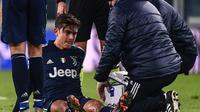 Striker Juventus, Paulo Dybala mendapat penanganan dari tim medis usai mengalami cedera dalam laga lanjutan Liga Italia Serie A 2020/21 pekan ke-17 melawan Sassuolo di Juventus Stadium, Minggu (10/1/2021). Juventus menang 3-1 atas Sassuolo. (AFP/Marco Bertorello)
