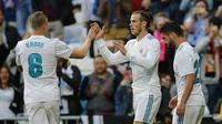 Striker Real Madrid, Gareth Bale, melakukan selebrasi bersama Toni Kroos usai mencetak gol ke gawang Celta Vigo pada laga La Liga di Stadion Santiago Bernabeu, Sabtu (12/5/2018). Real Madrid menang 6-0 atas Celta Vigo. (AP/Paul White)