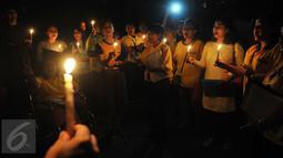 Sejumlah karyawan Artha Graha berkumpul sambil memegang lilin pada peringatan Hari Bumi atau Earth Hour di kawasan SCBD Jakarta saat lampu-lampu di kawasan itu mulai dipadamkan selama satu jam pada Sabtu malam (19/3/2016). (Foto: Istimewa)