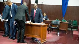 Anggota parlemen memindahkan meja menjauhi genangan air hujan yang membasahi lantai Gedung Parlemen Haiti, Port-au-Prince, Haiti, Rabu (21/8/2019). Saat kejadian, anggota parlemen sedang memperdebatkan proses impeachment Presiden Haiti Jovenel Moise atas tuduhan korupsi. (AP Photo/Dieu Nalio Chery)