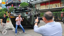 Sejumlah warga melakukan selfie dengan latar belakang Panser Anoa milik TNI di LTC Glodok, Jakarta, Jumat (4/11). Pengamanan ini merupakan bentuk kerja sama antara TNI-Polri dalam menjaga keamanan terkait demo bela islam . (Liputan6.com/Angga Yuniar)