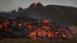 Aliran lava dari letusan gunung berapi di Semenanjung Reykjanes di barat daya Islandia pada Sabtu (20/3/2021). Erupsi Gunung berapi yang tertidur lama alias tidak aktif selama 6.000 tahun tidak mempengaruhi lalu lintas penerbangan. (AP Photo/Marco Di Marco)