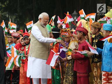 Perdana Menteri (PM) India, Narendra Modi didampingi Presiden Joko Widodo (Jokowi) bersalaman dengan murid Sekolah Dasar berpakaian adat Indonesia dalam upacara penyambutan di Istana Merdeka, Jakarta, Rabu (30/5). (Liputan6.com/Angga Yuniar)