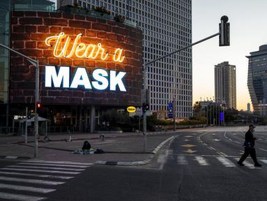 Seorang pria menyeberang jalan di samping papan reklame yang menyerukan agar orang-orang memakai masker selama lockdown nasional menyusul langkah-langkah pemerintah untuk membantu menghentikan penyebaran virus corona COVID-19 di Tel Aviv, Israel, Jumat (8/1/2021). (AP Photo/Oded Balilty)