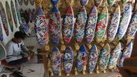 Pengrajin membuat sovenir papan seluncur di Bali, Senin (15/10). Menteri Koordinator Bidang Perekonomian Darmin Nasution meminta pelaku usaha sektor pariwisata dapat memanfaatkan KUR dengan bunga 7%. (Liputan6.com/Angga Yuniar)