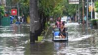 Becak berpenumpang seorang wanita melintasi banjir di kawasan Duta, Jelambar, Jakarta Barat, Selasa (5/3). Sejumlah ruas jalan di Jakarta Barat tergenang air akibat luapan Kali Angke dan drainase yang buruk serta pasang air laut. (merdeka.com/Arie Basuki)