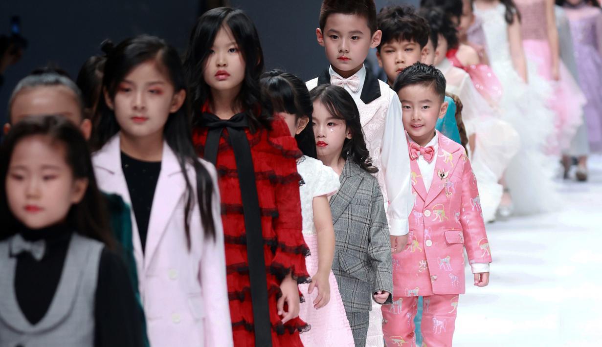 Model anak-anak membawakan busana rancangan KUNJIE oleh Liu Shuming  pada gelaran China Fashion Week di Beijing, China, Selasa (27/10/2020). (STR / AFP)
