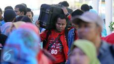 Seorang pemudik memanggul barang bawaannya di Stasiun Senen Jakarta, Sabtu (2/7). Ribuan pemudik kembali memadati Stasiun Senen untuk berangkat menuju kota kota di pulau Jawa. (Liputan6.com/Helmi Fithriansyah)