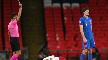 Bek Inggris Harry Maguire (kanan) mendapat kartu merah setelah menjegal penyerang Denmark, Kasper Dolberg (tengah) dalam lanjutan pertandingan UEFA Nations League grup A2 di stadion Wembley di London (14/10/2020). Inggris takluk atas Denmark 0-1. (AFP/Pool/Daniel Leal-Olivas)