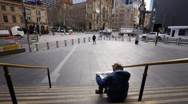 Seorang pria membaca koran di tangga Stasiun Flinders Street di Melbourne, Australia, Rabu (11/8/2021). Lima juta orang di kota terbesar kedua di Australia tersebut akan tetap berada di bawah perintah tinggal di rumah, setidaknya selama seminggu lagi. (AAP Image/Daniel Pockett)