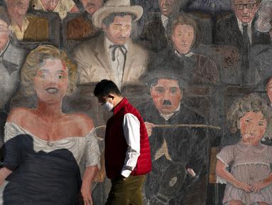 Seorang pria yang memakai masker berjalan melewati mural di bagian Hollywood Los Angeles, California, Amerika Serikat, Kamis (12/11/2020). California menjadi negara bagian kedua selain Texas yang mencatat 1 juta kasus infeksi virus corona COVID-19. (AP Photo/Jae C. Hong)