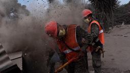 Tim penyelamat menggali tumpukan debu untuk mencari korban dari letusan gunung Feugo di desa San Miguel Los Lotes, Guatemala (5/6). Kemungkinan korban tewas dilaporkan akan terus bertambah. (AFP/Johan Ordonez)