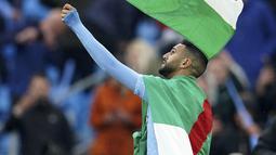 Gelandang Manchester City, Riyad Mahrez mengibarkan bendera Palestina saat merayakan timnya meraih gelar Liga Inggris di stadion Etihad, Minggu (23/5/2021). Pemain Aljazair ini melakukan hal tersebut bentuk dukungan kepada Palestina di tengah konflik dengan Israel. (AP Photo/Dave Thompson, Pool)