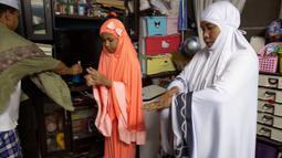 Keluarga Muslim Thailand menggunakan cairan desinfektan sebelum berdoa di ruang tamu rumah mereka di Bangkok, 28 April 2020. Banyak tempat ibadah ditutup guna membendung penyebaran Virus Corona COVID-19 ketika Umat Muslim di seluruh dunia menyambut bulan suci Ramadan. (AP Photo/Gemunu Amarasinghe)