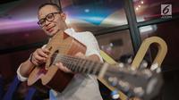 Menteri Ketenagakerjaan M. Hanif Dhakiri berpose dengan gitar sebelum tampil menjadi bintang tamu dalam acara KLY Lounge di Gedung KLY, Gondangdia, Jakarta, Jumat (5/10). (Liputan6.com/Faizal Fanani)