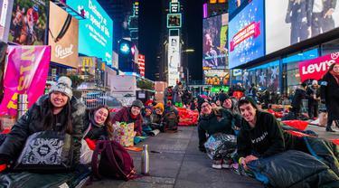 Orang-orang menghabiskan malam dengan tidur di area terbuka dalam acara World's Big Sleep Out di Times Square, New York, 7 Desember 2019. Aksi di beberapa kota besar dunia ini sebagai bagian dari upaya penggalangan dana untuk membantu para tunawisma di banyak negara. (Charles Sykes/Invision/AP)