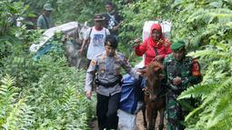 Polisi dan tentara mengawal petugas Pemilu 2019 yang menaiki kuda untuk mendistribusikan logistik ke TPS di desa-desa terpencil di Tempurejo, Jawa Timur, Senin (15/4). Petugas membawa kotak suara dan perlengkapan pemilu lainnya. (AP Photo/Trisnadi)