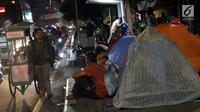 Pencari suaka duduk-duduk di luar tenda di atas trotoar depan Masjid Ar-Rayan, Jalan Kebon Sirih, Jakarta, Jumat (5/7/2019). Para pencari suaka ini membangun tenda-tenda dan meminta kepastian perlindungan dari UNHCR . (Liputan6.com/Helmi Fithriansyah)