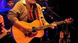 Iwan Fals memainkan gitarnya sambil bernyanyi dalam konser bertajuk Untukmu Indonesia di Istora Senayan, Jakarta, Sabtu (21/11). Iwan Fals membawakan sebanyak 23 lagu pada konser tersebut. (Liputan6.com/Faisal R Syam)
