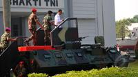 Presiden Joko Widodo saat menaiki Panser Anoa untuk menghadiri upacara pengangkatan dirinya sebagai warga kehormatan pasukan khusus TNI, Kamis (16/4/2015). (Liputan6.com/Yoppy Renato)