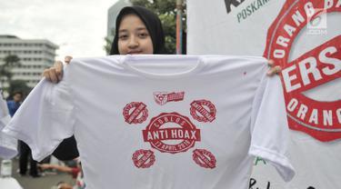 Relawan menunjukkan kaus Anti Hoax saat kampanye Pemilu Damai pada CFD di kawasan Bundaran HI, Jakarta, Minggu (17/3). Kampanye yang digelar Gerakan Kebijakan Pancasila mengajak masyarakat untuk menjaga pemilu dari hoax. (merdeka.com/Iqbal S Nugroho)