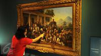 Pengunjung memperhatikan lukisan karya Raden Saleh berjudul Penangkapan Pangeran Diponegoro tahun 1857 yang dipamerkan di Galeri Nasional, Jakarta, Senin (1/8). (Liputan6.com/Gempur M Surya)