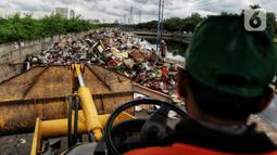 Petugas PPSU menggunakan alat berat mengumpulkan sampah sisa banjir di sepanjang Kali Cengkareng, Jakarta Barat, Kamis (9/1/2020). Tumpukan sampah di sepanjang bantaran kali dan rumah-rumah warga terlihat setelah banjir yang melanda sejumlah kawasan Jakarta mulai surut. (Liputan6.com/Johan Tallo)