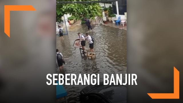 Dua siswa sekolah di Thailand bekerja sama melewati banjir agar sepatu mereka tidak basa. Mereka menggunakan kursi sekolah secara bergantian.