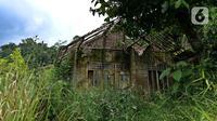 Sebuah bangunan ditumbuhi tanaman liar di Kampung Cigobang, Lebak, Banten, Sabtu (20/3/2021). Pascabencana banjir bandang dan longsor yang terjadi di Kampung Cigobang pada 1 Januari 2020 lalu mengakibatkan sekitar 154 kepala keluarga (KK) meninggalkan kampung tersebut. (Liputan6.com/Herman Zakharia)