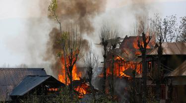 Sejumlah bangunan tempat tinggal terbakar akibat pertempuran senjata antara kelompok militan dan pasukan keamanan India di Shopian, Srinagar (4/1). Situasi wilayah ini kian memanas dan sering terjadi bentrokan. (AP Photo / Mukhtar Khan)