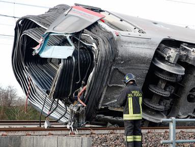 Seorang petugas pemadam kebakaran memeriksa gerbong kereta yang tergelincir, dekat Lodi, Italia utara, Kamis (6/2/2020). Kereta berkecepatan tinggi itu keluar dari rel hingga menewaskan sedikitnya dua orang dan sekitar 30 lainnya luka dalam insiden itu. (AP/Antonio Calanni)