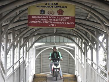 Pengendara sepeda motor melintasi rambu larangan saat melewati jembatan penyeberangan orang (JPO) Stasiun Pasar Minggu Baru, Jakarta, Selasa (10/3/2020). JPO tersebut kerap digunakan pengendara sepeda motor untuk menyeberang meski rambu larangan sudah dipasang. (merdeka.com/Iqbal Nugroho)