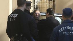 Aparat kepolisian mengamankan Seif Eldin Mustafa untuk dibawa ke pengadilan di Larnaca, Siprus, Rabu (30/3). Pria Mesir itu mengalihkan perjalanan pesawat rute Alexandria-Kairo dan menyandera beberapa penumpang. (REUTERS/Yiannis Kourtoglou)