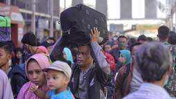 Sejumlah pemudik mengantre di pintu keberangkatan Stasiun Pasar Senen, Jakarta, Selasa (12/6). Pada H-3 Lebaran, sebanyak 25.295 pemudik berangkat ke berbagai daerah di Pulau Jawa melalui Stasiun Pasar Senen. (Liputan6.com/Faizal Fanani)