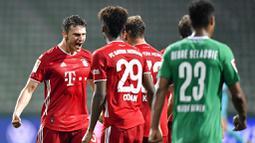 Pemain Bayern Munchen, Joshua Kimmich, merayakan kemenangan atas Werder Bremen pada laga Bundesliga di Weserstadion, Bremen, Selasa (16/6/2020). Bayern Munchen menang dengan skor 1-0 atas Werder Bremen. (AP/Martin Meissner)