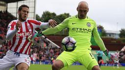 Kiper Manchester City, Willy Caballero, berusaha mengamankan bola dari jangkauan pemain Stoke, Ramadan Sobhi. Pelatih City, Pep Guardiola, kembali menjadikan Joe Hart sebagai cadangan dan memilih memainkan Caballero. (AFP/Lindsey Parnaby)