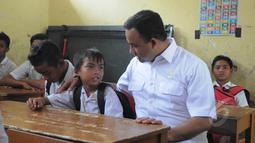 Mendikbud Anies Baswedan berbincang dengan seorang pelajar ketika mengunjungi SDN 1 Pajagan, Lebak, Banten, Senin (16/3/2015). Sebanyak 44 siswa SD terjatuh ke Sungai Cibeurang akibat jembatan yang mereka lewati putus. (Liputan6.com/Herman Zakharia)